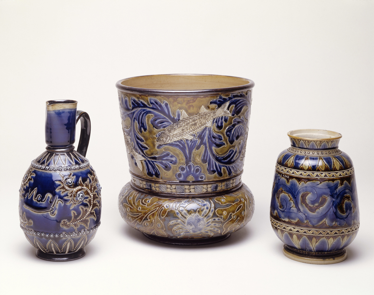 "Selection of three blue glaze stoneware jugs. On the left is a stoneware jug, decorated with a blue glaze and a foliate decoration which is incised and applied. This sample is Inscribed ""Mary"" and was inscribed by Queen Mary when she was twelve years old. A silver colour has been applied to the base of the neck and base. In the centre is a flower pot glazed green and brown decorated with marine subjects. Stamped on the base 'Doulton Lambeth' and '1881', and inscribed with a monogram of one horizontal line with 3 vertical lines incised across it. On the right is a jar decorated with a band of foliage in blue on a dark brown background. The decoration is incised and applied. On the base is stamped 'Doulton Lambeth 1874' and inscribed with a monogram 'EJE' which stands for Emily J Edwards."